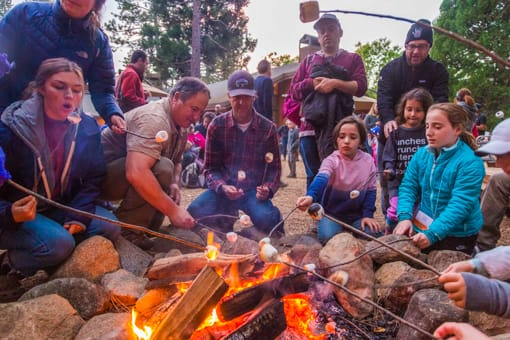Adults and children roasting marshmallows at Family Camp