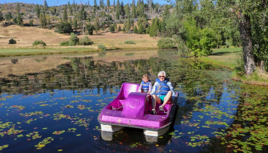 Grandmother and grandchild on boat in pond
