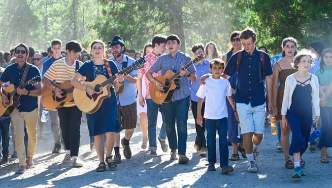 Campers walking with guitars and singing