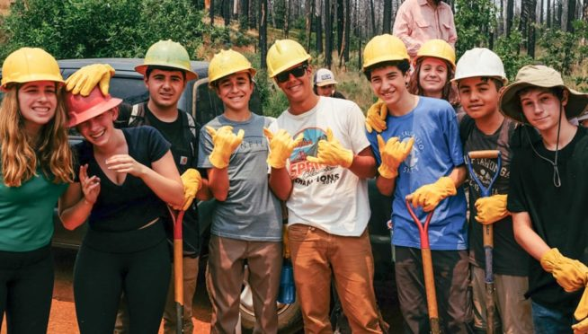 Teens smiling with yellow hard hats and gloves at Teen Leadership event