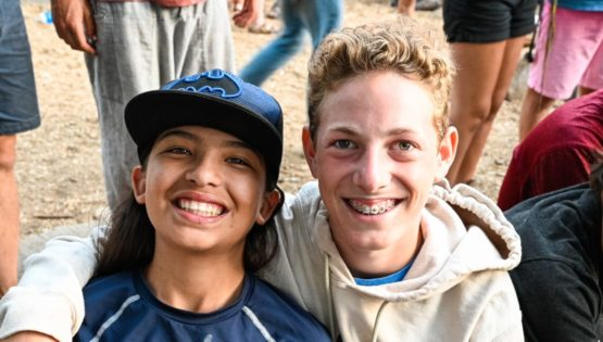 Young camper smiling with staff