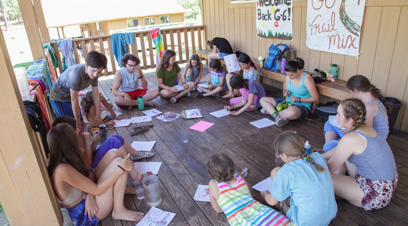Campers sitting in circle playing games in bunk