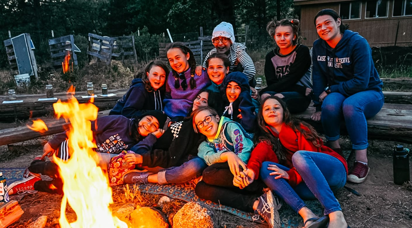 Girls by campfire