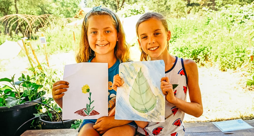 Girls holding nature drawings