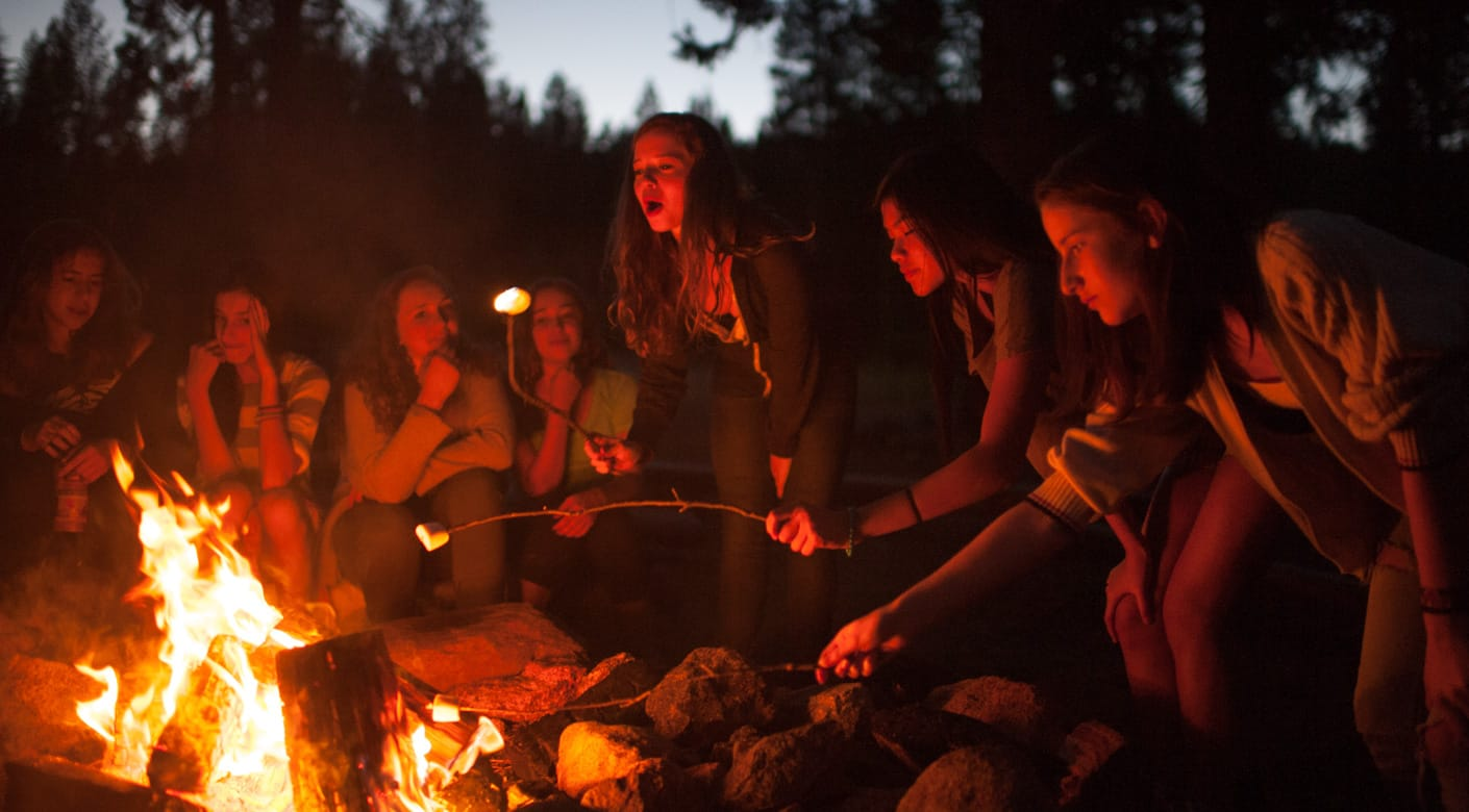 Counselors in training at a campfire
