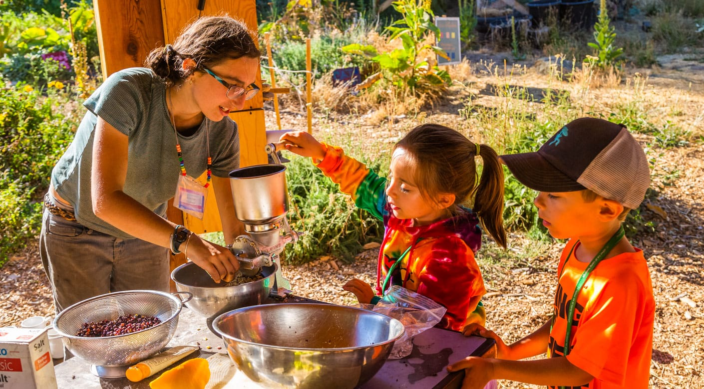 Staff and kids cooking outdoors for the Family Camp program