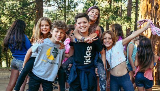Campers giving piggyback rides and smiling