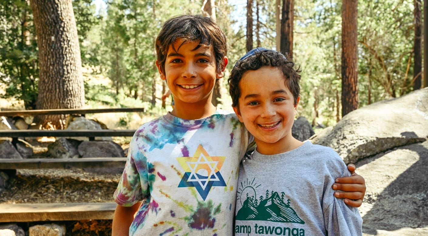 Two young campers smiling outside
