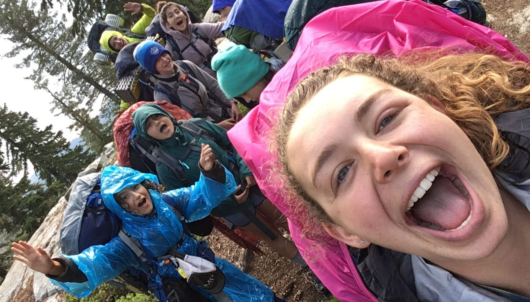 Teens taking a group selfie with backpacks on at the Women of the Wild quest