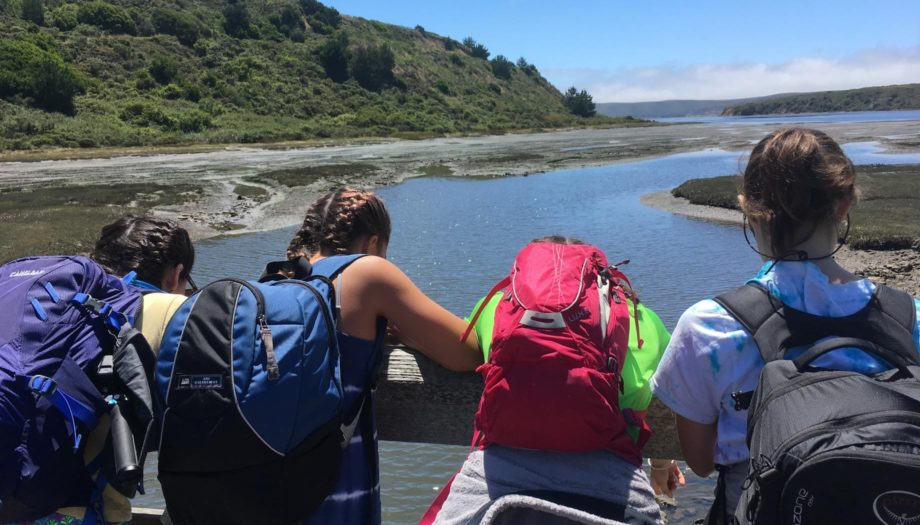 Teens hiking and admiring view of water on the Women of the Wild quest